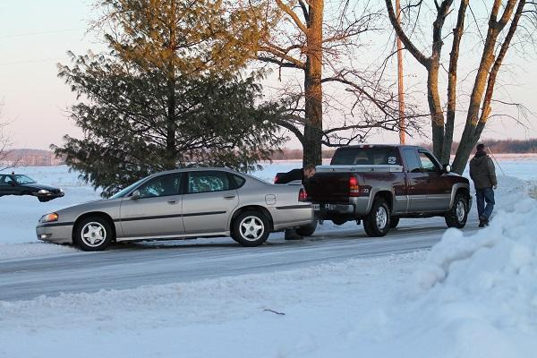 Sophomore Alexis Neidlinger gets a tow from her brother, Austin, after sliding off the road in front of CHS.  Icy road conditions often create the need for school delays or cancellations.