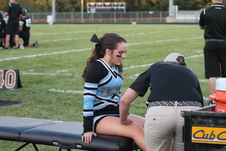Junior+cheerleader+Morgan+Stack+is+checked+out+by+a+trainer+during+a+home+football+game.