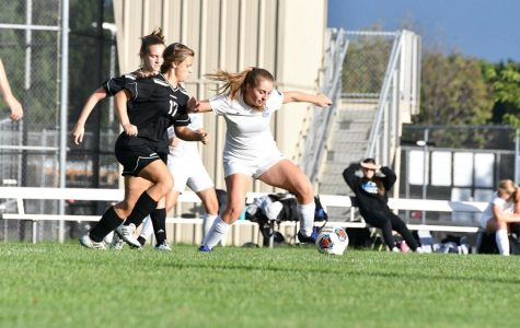 Senior Abigail Kinkle shields off a defender while moving up the pitch
